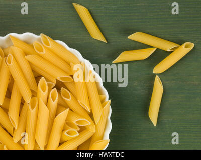 Dish of Uncooked Italian Style Penne Pasta Against a Green Background - Stock Photo