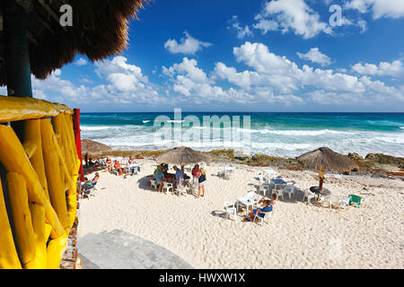 Sunny day with cloudy sky on sand beach with straw umbrellas and tourists on Cozumel - Stock Photo