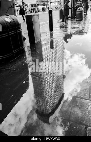London black and white urban photography: Centre Point building reflected in puddle. London, UK - Stock Photo
