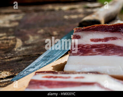 Tasty bacon on the table with knife for cutting close up - Stock Photo