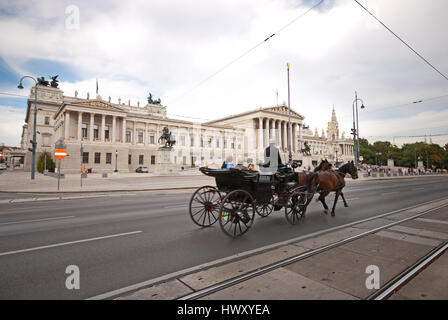 A horse-drawn carriage called fiaker passes by the Austrian Parliament on the Ringstrasse in Vienna. - Stock Photo