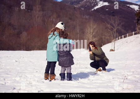 Mother taking picture of two children in winter landscape - Stock Photo