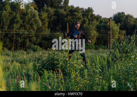 Businessman running with laptop in the nature - Stock Photo