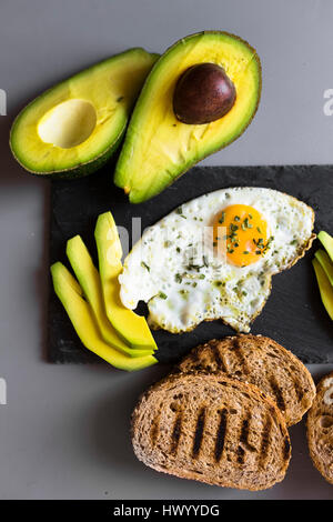 Breakfast with eggs, avovados and toasted bread - Stock Photo