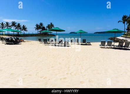 Sunshade umbrella and chairs on a beach in Kota Kinabalu, Sabah Borneo, Malaysia. - Stock Photo