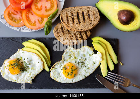 Breakfast with eggs, avovados, tomatoes and toasted bread - Stock Photo