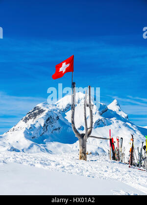 Switzerland, Canton of Bern, Grindelwald, Swiss flag with Reeti in background - Stock Photo