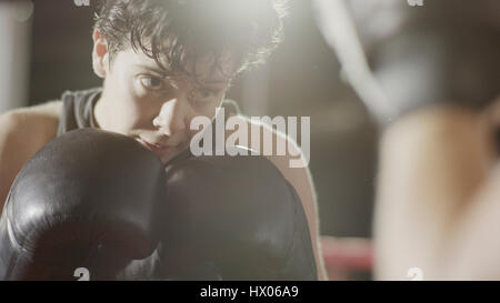 Close up of female boxer protecting her face standing in boxing ring during match - Stock Photo