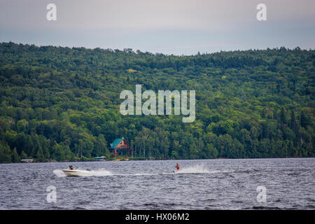 boat and skier on a lake in summer - Stock Photo
