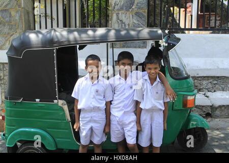 Sri Lankan schoolboys in front of a Tuk Tuk in Galle - Stock Photo