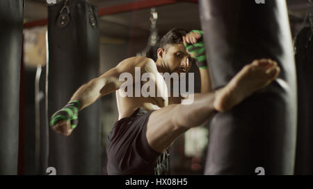 Selective focus view of man kickboxing punching bag in gym - Stock Photo
