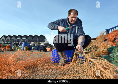 Fisherman in Whitstable, Kent, UK mending nets by hand. - Stock Photo
