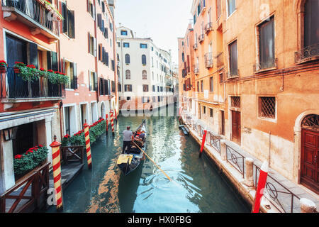 Gondolas on canal in Venice. Venice is a popular tourist destination of Europe - Stock Photo