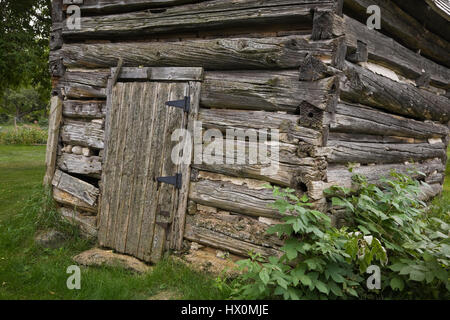Partial view of an old 1800s hewn log storage shed. - Stock Photo