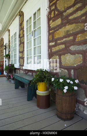 Partial view of decorated veranda of 1831 cottage style quarry stone house exterior. - Stock Photo