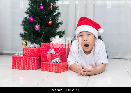 Asian Chinese little boy showing funny expression with Christmas presents in the living room at home. - Stock Photo