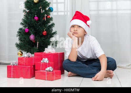 Asian Chinese little boy showing bored expression with Christmas presents in the living room at home. - Stock Photo