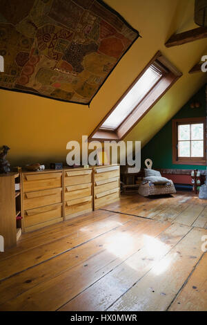 Yellow rustic master bedroom with wooden dresser in 1840 Canadiana old house interior.