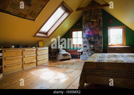 Yellow rustic master bedroom with bed and furnishings in 1840 Canadiana old house interior.