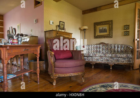 Antique upholstered armchair with table and floral sofa in yellow and pink living room of 1741 old house interior. - Stock Photo