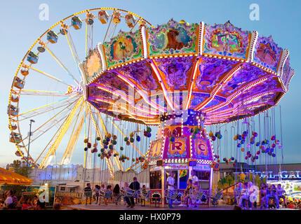 Illuminated swing carousel and Ferris wheel, Cranger Kirmes, the largest folk festival in the Ruhr district, Herne - Stock Photo