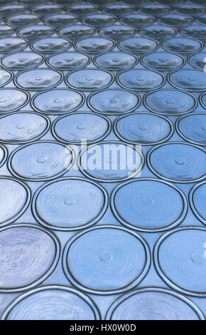 Azure window with circular panes of swirled glass. Shallow depth of field. - Stock Photo