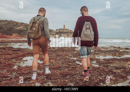 Spain, Oropesa del Mar, two young men walking on stony beach - Stock Photo