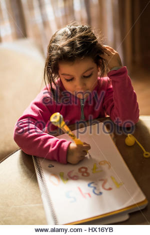 Little girl drawing numbers - Stock Photo