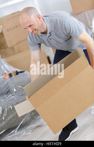 man painfully carrying boxes - Stock Photo