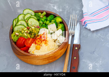 Bowl of bright healthy vegan lunch: vegetable salad with tofu, hummus and guacamole. Buddha rainbow wooden bowl, - Stock Photo