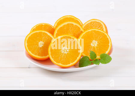 plate of halved oranges on white background - Stock Photo