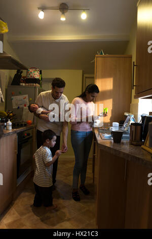 Young family in the kitchen. The mother is washing dishes while the father is holding their baby son and tending - Stock Photo