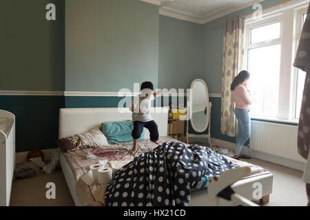 Little boy is jumping on his mother's bed, who is standing by the window with her baby son in her arms. - Stock Photo