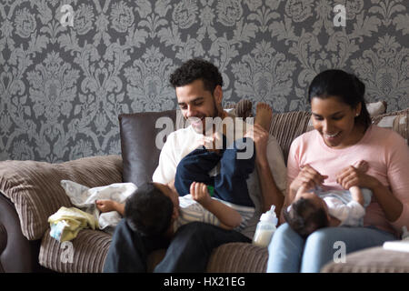 Elder brother is copying his little brother. They are lying on their parents laps with their feet in the air, on - Stock Photo