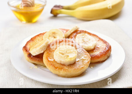 Pancakes with cottage cheese and banana slices, healthy breakfast, close up view - Stock Photo