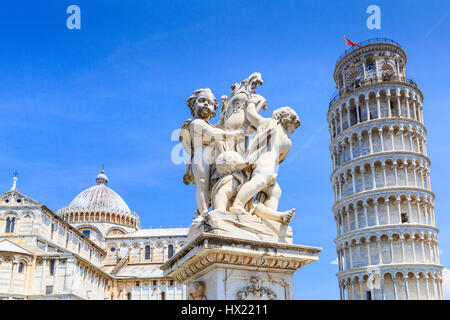 Pisa, Italy. The Pisa Cathedral, the Fountain with angels, and the Leaning Tower of Pisa in Piazza dei Miracoli. - Stock Photo
