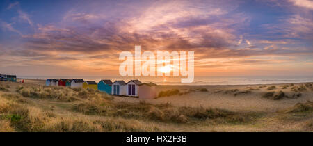On a calm dawn in mid March, the sun rises over the famous line of beach huts on the dunes at the Suffolk seaside - Stock Photo