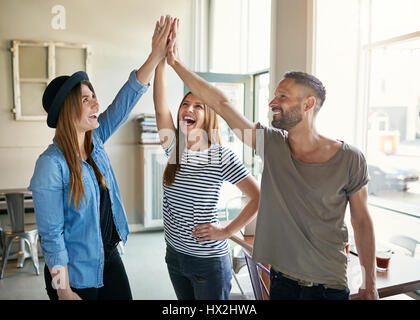 Young smiling trendy co-workers making gesture of high five in light spacious office. - Stock Photo