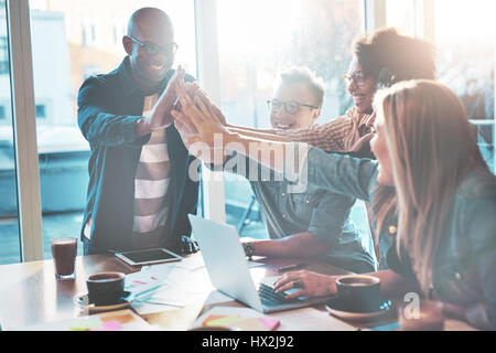 Group of happy high fiving coworkers at table in office. Bright large window in background. - Stock Photo