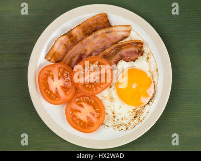 Bacon Egg and Tomato Breakfast Food Against a Green Background - Stock Photo