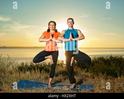 smiling couple making yoga exercises outdoors - Stock Photo