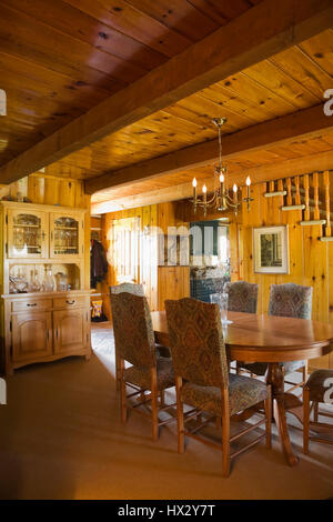 Antique table with upholstered high back chairs and buffet in dining room of 1977 log home interior - Stock Photo