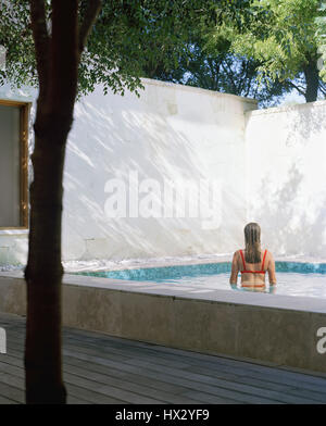 Back view of woman in pool , Turks and Caicos - Stock Photo