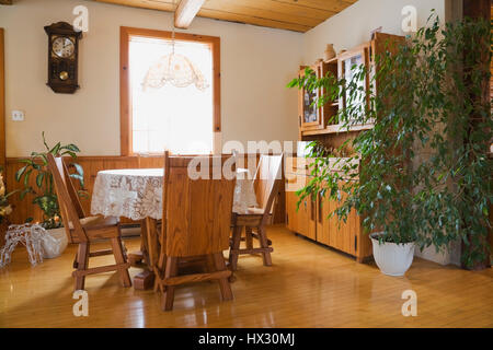 Dining room with hewn table and chairs plus a buffet inside a 1982 reconstructed old log home interior - Stock Photo