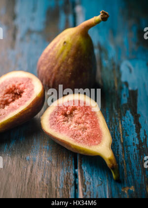 Close-up of figs on distressed wooden tabletop - Stock Photo