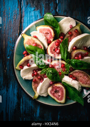 Figs with Mozzarella and Pomegranate Seeds on distressed wooden tabletop - Stock Photo