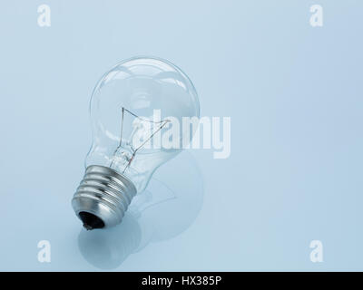 The light bulb lies on a glossy surface on a light blue background. Reflection of a light bulb. - Stock Photo