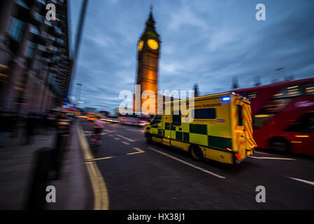 An ambulance traveling at speed at dusk with blue lights flashing past the Houses of Parliament in London passing - Stock Photo