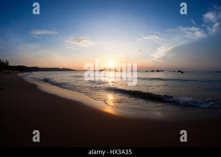 Silhouette of several small fishing boats at sea seen from sandy beach in the morning during golden colored sunrise - Stock Photo