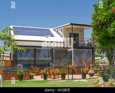 Modern two storey house with verandah, outdoor spa, paved garden area, solar panels on roof & shading tree under - Stock Photo